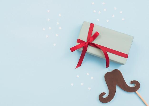 Composición de caja de regalo y palo bigote.
