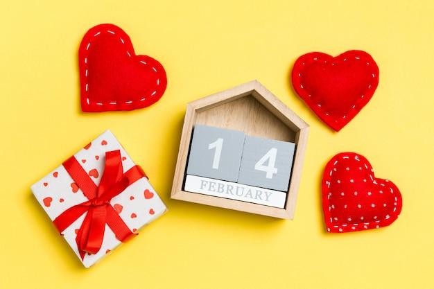 Composición de calendario de madera, cajas de regalo blanco de vacaciones y corazones textiles rojos sobre fondo colorido. el catorce de febrero. concepto de san valentín