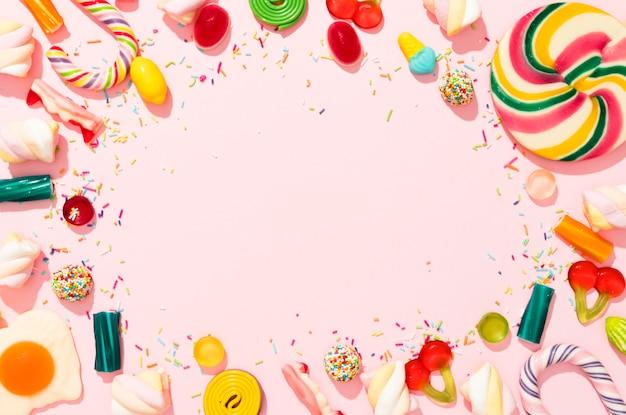 Composición de caramelos de colores sobre fondo rosa con espacio de copia