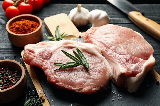 Composición con carne cruda para bistec e ingredientes en la mesa de madera
