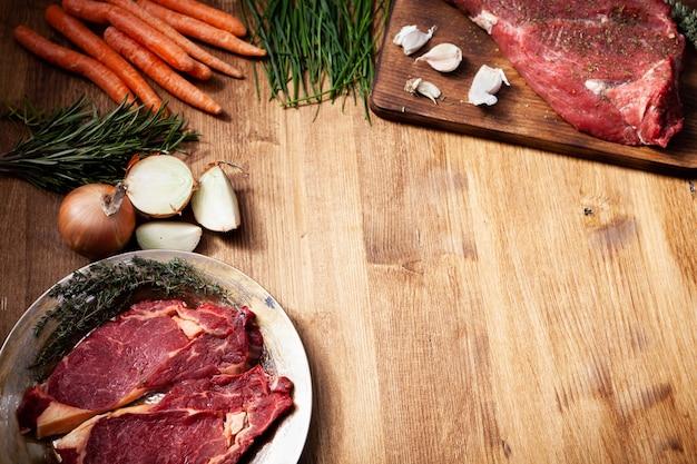 Composición con carne cruda y diferentes verduras en mesa de madera. romero verde. cebolla blanca. carne roja.