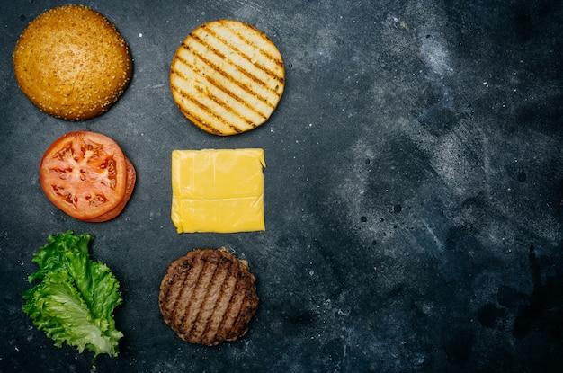 Composición casera de hamburguesas (receta). productos para la hamburguesa clásica sobre un fondo oscuro.