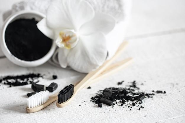 Composición con cepillos de dientes naturales de madera, polvo blanqueador de dientes negros y espacio de copia de flores de orquídeas.