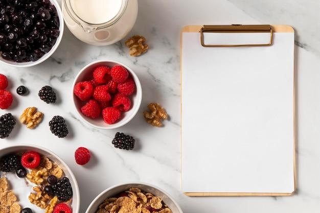 Composición de cereales tazón de fuente saludable con bayas con portapapeles vacío