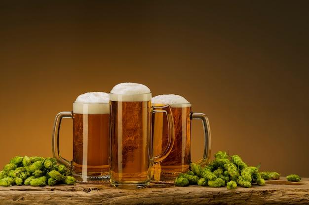 Composición con cerveza light con espuma en vasos y lúpulo y trigo en la mesa, espacio libre para texto