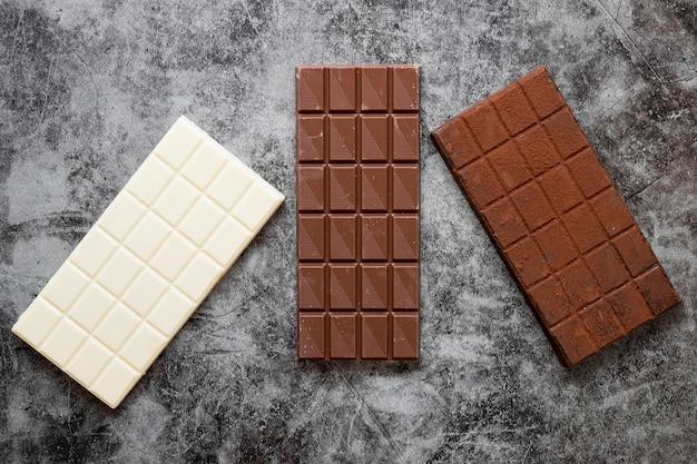 Composición de chocolate creativa plana en fondo oscuro