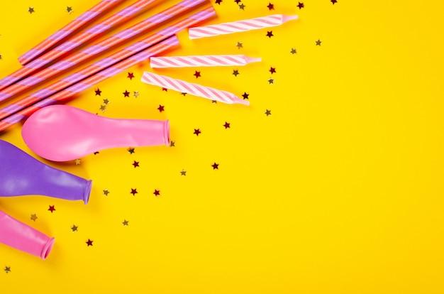 Composición coloreada de las pajas de beber y de los balones de aire en la decoración amarilla del fondo, del partido y de la celebración.