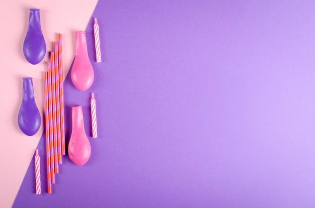 Composición coloreada de las velas y de los balones de aire en la decoración púrpura del fondo, del partido y de la celebración.