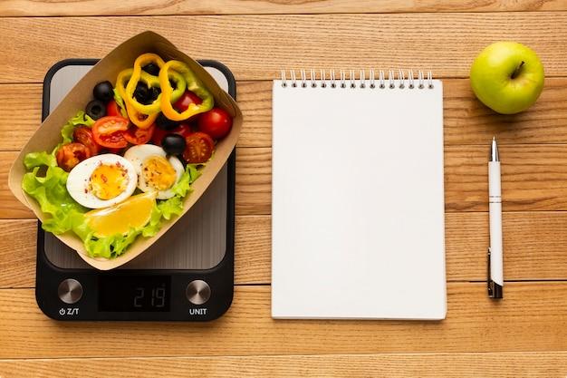 Composición de comida sabrosa vista superior con cuaderno vacío