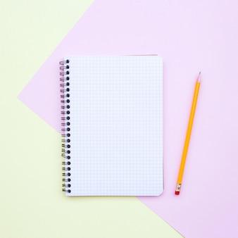 Composición de composición plana mínima con cuaderno vacío con lápiz sobre fondo amarillo y rosa