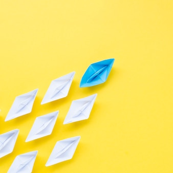 Composición para el concepto de individualidad con barcos de papel sobre fondo amarillo