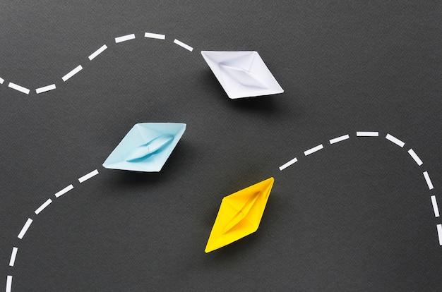 Composición para el concepto de individualidad con barcos de papel sobre fondo negro