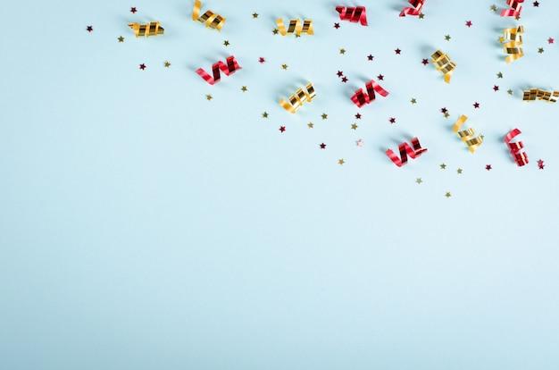 Composición de confeti de colores sobre fondo azul, decoración de fiesta y celebración.