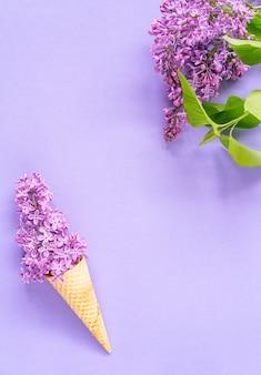 Composición de cono de helado con flores de color lilas púrpura. lay flat. vista superior. concepto creativo de verano