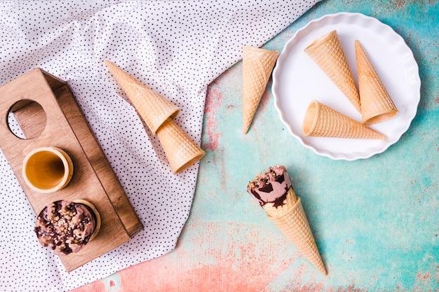Composición de copas de obleas vacías y helado en conos de waffle