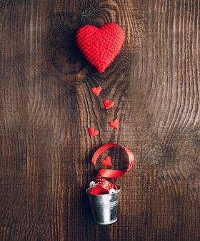 Composición de corazones de tejido y cubos decorativos sobre un fondo oscuro de madera