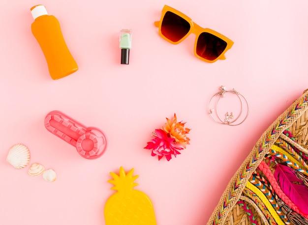 Composición con cosas de verano sobre fondo rosa.