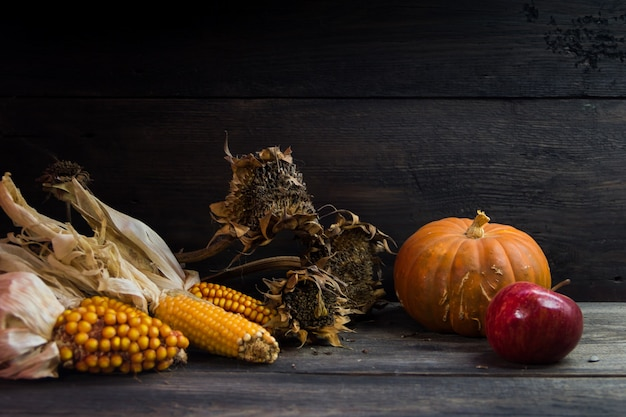 Composición de la cosecha de otoño con girasoles de calabaza de maíz y manzanas sobre fondo rústico