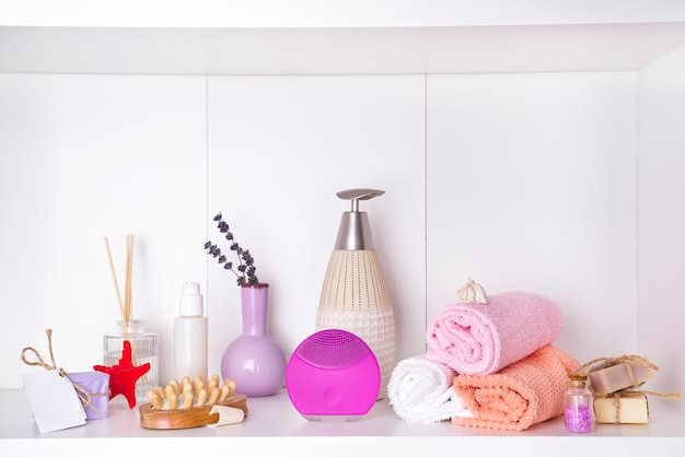 Composición con el cosmético del balneario, velas y cepillo para la cara, aislados en blanco