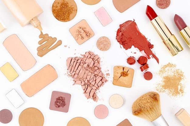 Composición con cosméticos coloridos sobre fondo blanco.
