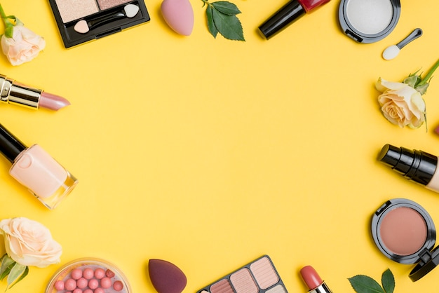 Composición de cosméticos con copia espacio sobre fondo amarillo.