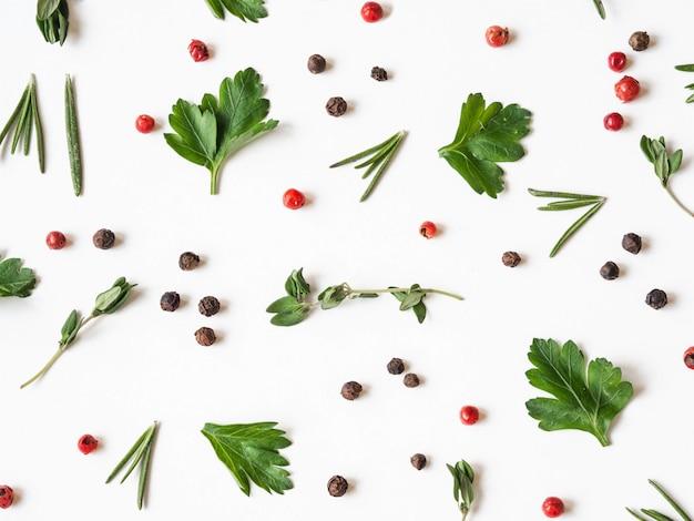 Composición creativa de alimentos decorativos de diversas especias y hierbas frescas sobre fondo blanco.