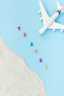 Composición creativa con un avión de juguete, arena y viajes de inscripción. concepto de viaje de vacaciones