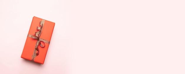 Composición creativa de caja de regalo con lazo de cinta dorada en rosa pastel.