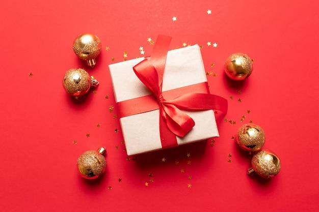 Composición creativa con caja roja presente, cintas, decoraciones navideñas doradas en rojo.