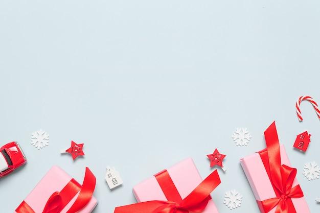 Composición creativa de cajas rosas con cintas de raso rojas, ramas de bayas y decoración de bolas de navidad.