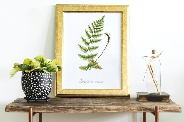 Composición creativa de diseño de interiores de casa con marco de póster, consola de madera, plantas en macetas y accesorios de diseño hipster