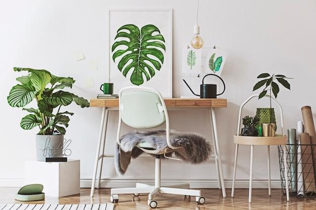 Composición creativa del diseño de interiores del espacio de trabajo doméstico con marco de póster, mesa, plantas en macetas y accesorios de diseño hipster
