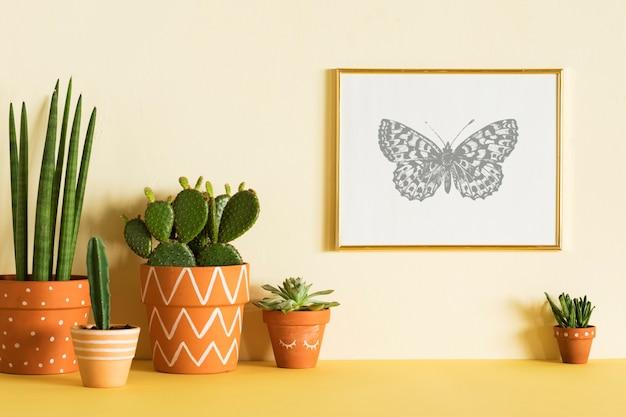 Composición creativa de diseño de interiores con estilo hipster con marco de póster y plantas en macetas de diseño