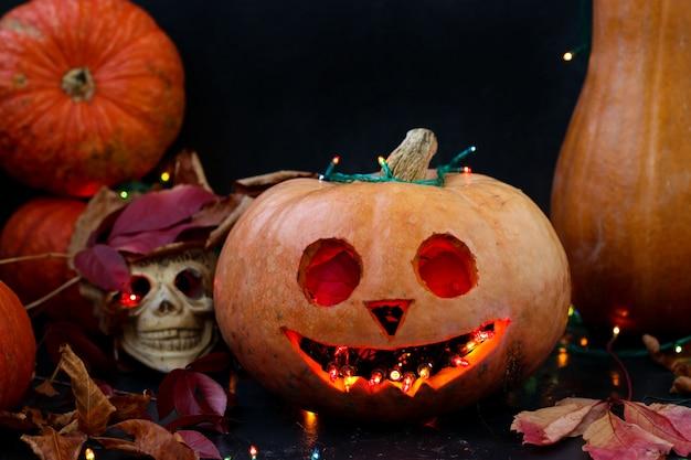 Composición creativa de halloween con una calavera y una calabaza de miedo en la oscuridad, de cerca,