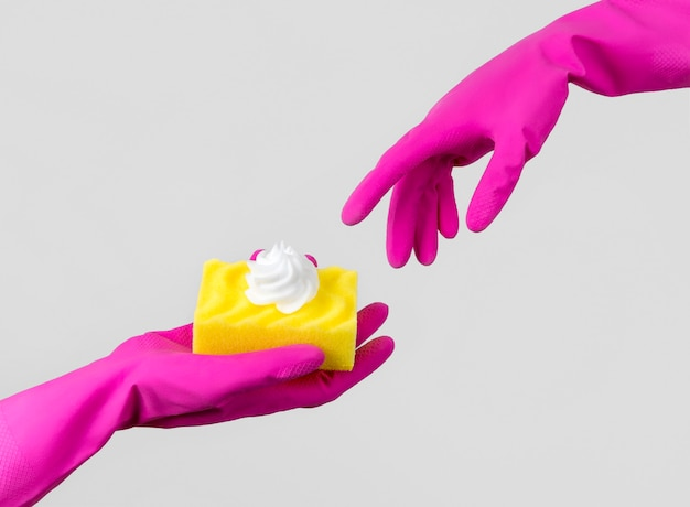 Composición creativa con mano femenina en un guante de goma rosa y esponja con espuma. servicio de limpieza o limpieza de diseño creativo.