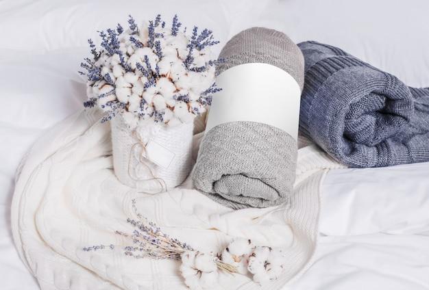 Composición creativa con mantas enrolladas, algodón y flores de lavanda.