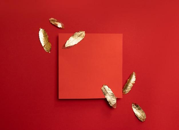Composición creativa con marco de hoja roja con hojas de oro sobre un fondo rojo.