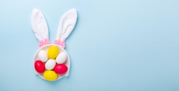 Composición creativa de pascua. huevos de pascua y orejas de conejo sobre fondo azul. copia espacio