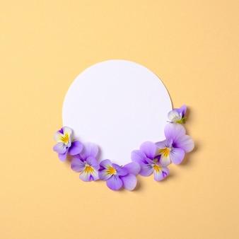 Composición creativa plana: círculo de papel en blanco y pétalos de flores sobre fondo amarillo. marco