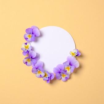 Composición creativa plana: círculo de papel en blanco y pétalos de flores sobre fondo amarillo.