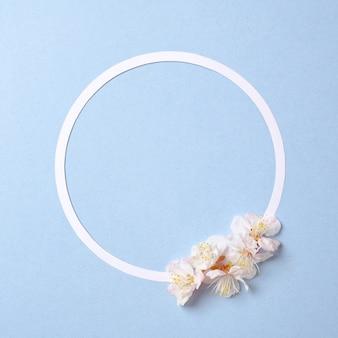 Composición creativa plana: círculo de papel en blanco y pétalos de sakura en flor
