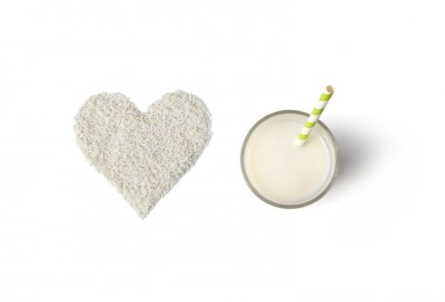 Composición creativa con vidrio, paja y arroz en forma de corazón aislado sobre fondo blanco.