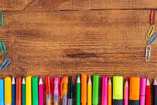 Composición con cuaderno en blanco página colorido lápiz, marcador y maqueta de pluma. de vuelta a la escuela