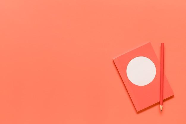 Composición de cuaderno rosa y lápiz rojo.