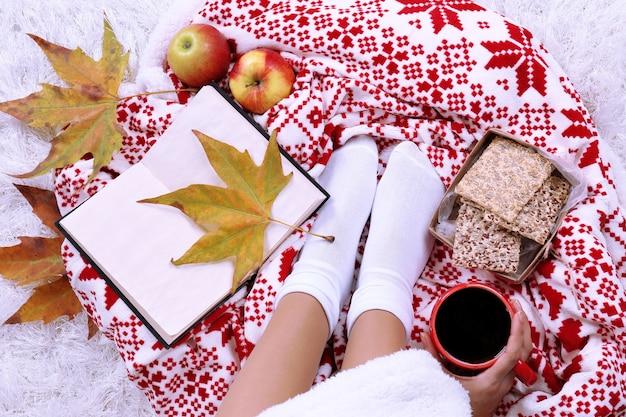 Composición con cuadros cálidos, libro, taza de bebida caliente y piernas femeninas, sobre fondo de alfombra de color