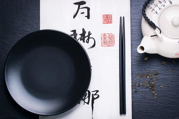 Composición de alimentos asiático con palillos chinos y plato vacío sobre un fondo oscuro piedra