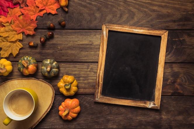 Composición de otoño con marco de pizarra y café