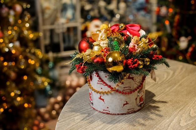 Composición decorativa navideña en caja con ramas de abeto decoradas con bolas de cristal rojo, cuentas, ángeles y arcos