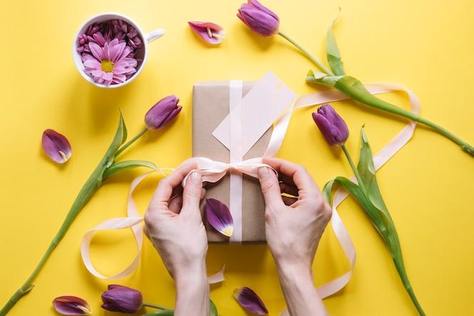 Composición del día de la madre con manos preparando caja de regalo