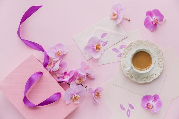 Composición delicada de flatlay con taza de café matutino con leche o capuchino, letras, bolsa de regalo rosa y flores de orquídeas sobre una superficie rosa claro. hermoso concepto de desayuno
